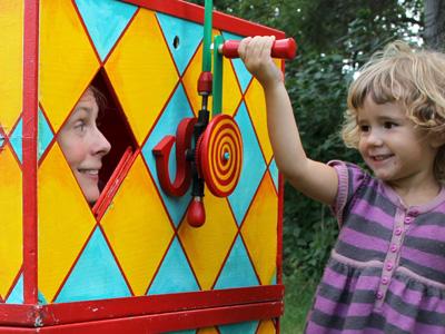 Ett barn vevar på en vev som sitter på en stor färgglad låda där ett ansikte tittar fram ur ett hål.